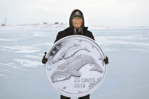 In Cape Dorset, Nunavut, artist Tim Pitsiulak holds a reproduction of the new 25-cent circulation coin he designed for the Royal Canadian Mint, celebrating life in the North.