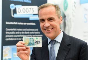 Bank of England Governor Mark Carney poses with the recently released £5 banknote depicting wartime leader Winston Churchill. (JOE GIDDENS/AFP/Getty Images)