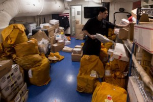 Logistics Specialist Seaman Devan Rodriguez sorts mail in the USS John C. Stennis' post office. (Photo provided)