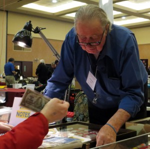 Nick Cowan, owner of The Coin Collector, helps someone find a banknote.