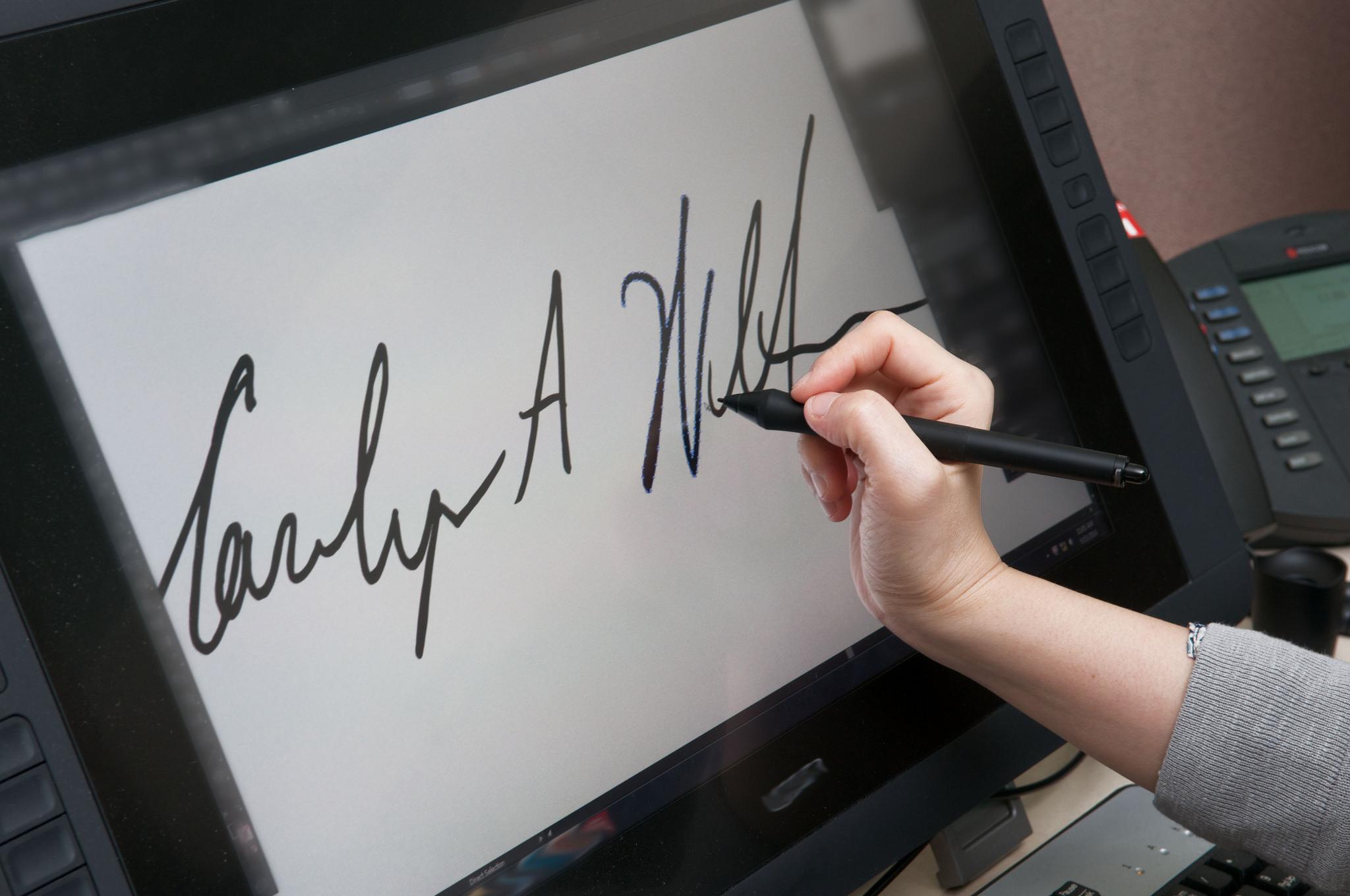 Senior Deputy Governor Carolyn Wilkins' signature goes digital as a designer prepares a bank note proof.